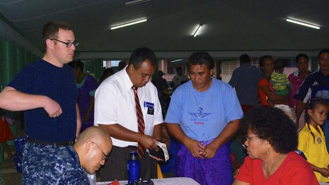 US navy personnel and Elder Gasio, missionary help patients with interpretation.