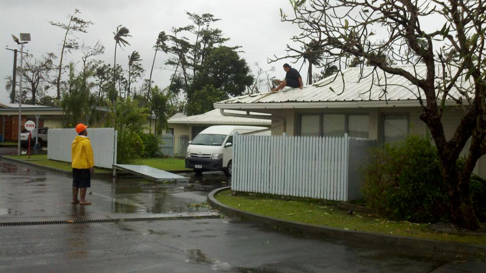 Repairing roof during lull in storm (Cyclone Evan 2012)