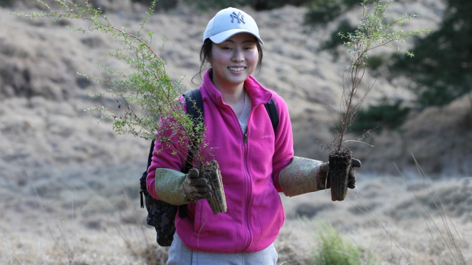 Lang-Ming-shows-some-of-the-shrubbery-to-be-planted-at-the-Wenderholm-Regional-Park-near-Auckland,-during-a-multi-day-.community-service-project-by-the-Pacific-Area-Office-staff.-New-Zealand,-June-2021