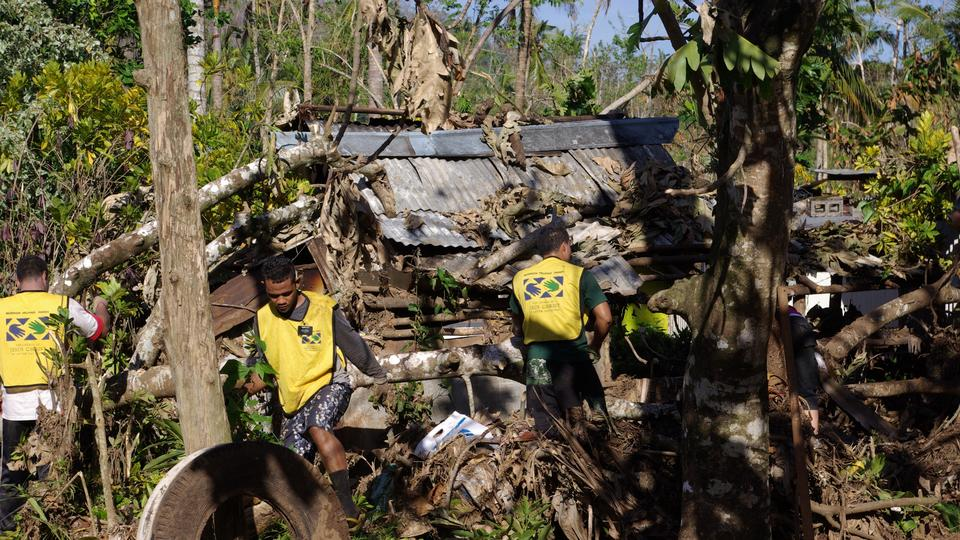 Mormon missionaries help a family clean up their home and yard after Cyclone Evan December 2012