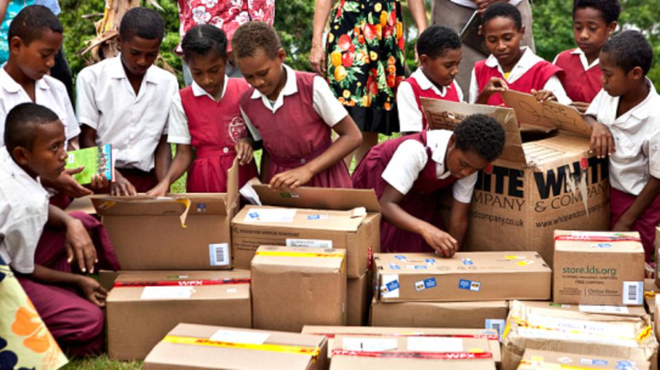 Children on the Fiji island of Bau unpack boxes of donated books for their school library